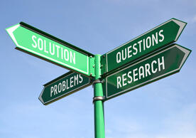 image of a street sign that says solution, problems, questions and research